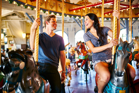 romantic couple riding carousel together on date Imagens