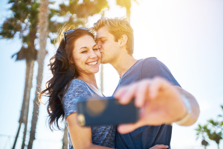 beach kiss: man kissing his girlfriend on the cheek for romantic selfie with lens flare and palm trees in background