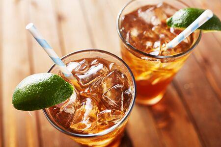 frio: dos copas frías de té helado con paja de papel gajos de lima retro en madera mesa. Disparo con un enfoque selectivo. Foto de archivo