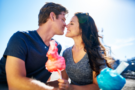 about: romantic couple about to kiss on date with cotton candy on sunny summer day