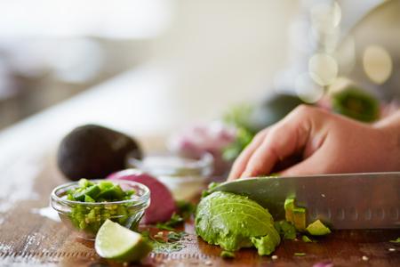 PrEP: cutting avocado with skin removed and dicing to prepare for guacamole recipe