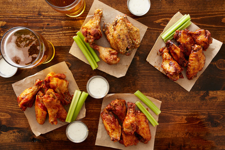 food dressing: many different flavored buffalo chicken wings with beer party sampler sharing platter shot from top down view