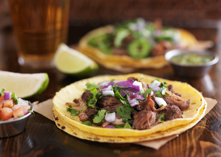 authentic mexican street tacos with barbacoa beef on yellow corn tortilla