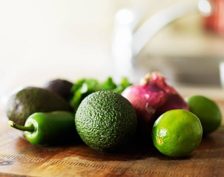 prep: all the ingredients needed to make guacamole laid out on wooden cutting board in kitchen Stock Photo