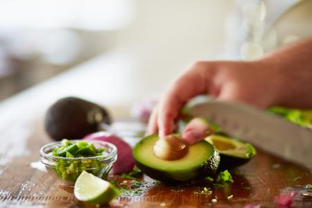 preparing avocado for guacamole recipe on wooden cutting board