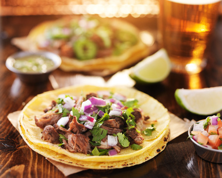 yellow corn: two mexican street tacos with barbacoa beef served on yellow corn tortilla with beer in background