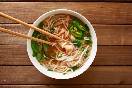 santa cena: comer un plato de carne pho vietnamita con los palillos superior derribado