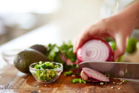cutting red onion on wooden board in kitchen to make guacamole