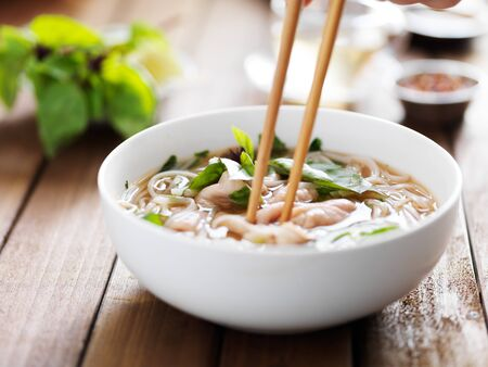 santa cena: comer un plato de carne pho con palillos