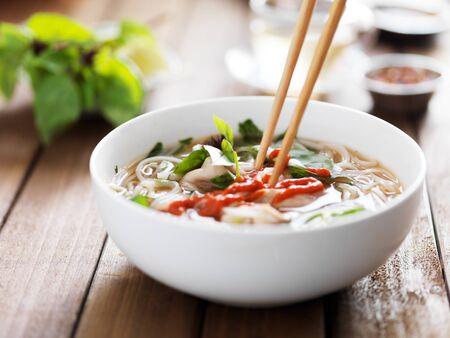 santa cena: comer un plato de carne pho vietnamita con los palillos y la salsa picante sriracha Foto de archivo