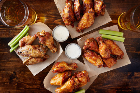 overhead view of four different flavored chicken wings with ranch dressing, beer, and celery sticks