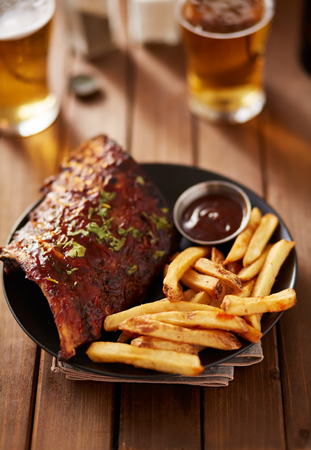 barbecue ribs: barbecue ribs with french fries and sauce on plate