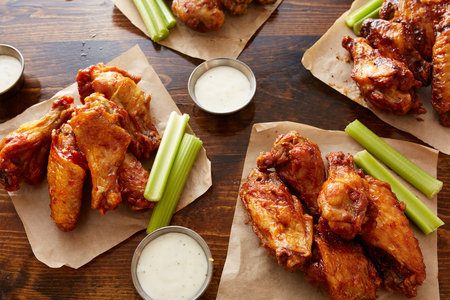 different flavored chicken wings with ranch dipping sauce and celery sticks on wooden table Reklamní fotografie - 46427028
