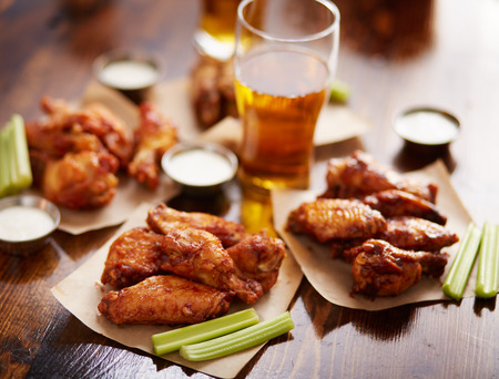 different flavored chicken wings on wax paper served with beer, ranch dressing and celery sticks Foto de archivo