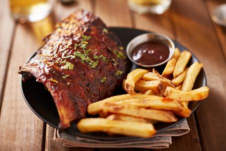 접시에 감자 튀김과 바베큐 돼지 갈비의 절반 랙 스톡 콘텐츠