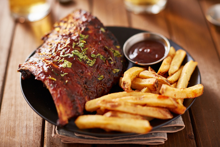 half rack of barbecue pork ribs with french fries on plate