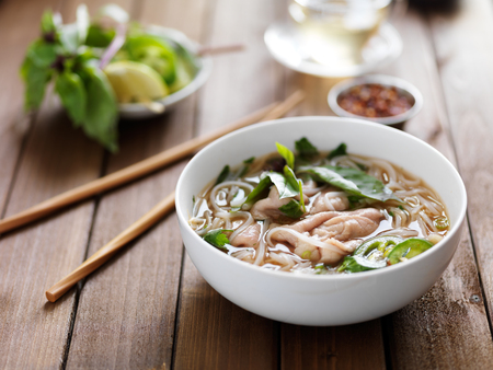 vietnamese food: vietnamese beef pho with chopsticks on wooden table