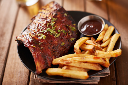 half rack barbecue rib platter with french fries on rustic wooden table Imagens