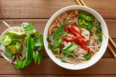 santa cena: pho de carne vietnanese con salsa Sriracha disparo desde vista a�rea en mesa de madera