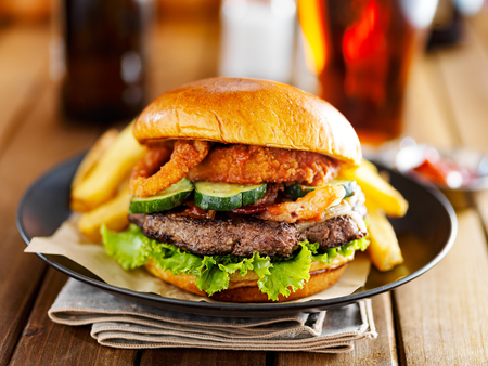 western food: western barbecue burger with onion rings and sauce served with french fries