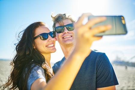 happy couple taking romantic selfie on beach with bright sun
