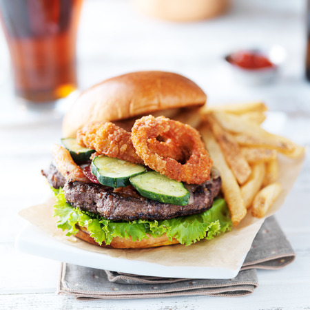 onion rings: bacon barbecue burger topped with onion rings on white table served with fries