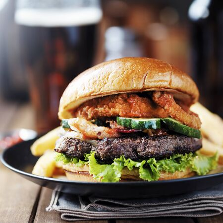 onion ring bacon barbecue burger with fries and beer Imagens