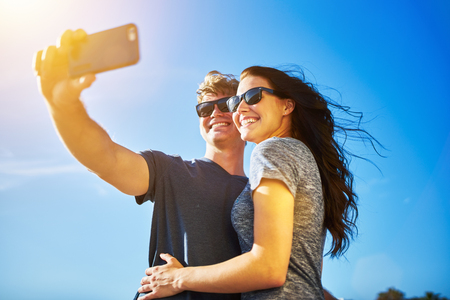 couple selfie with lens flare on clear summer day and wearing sunglasses