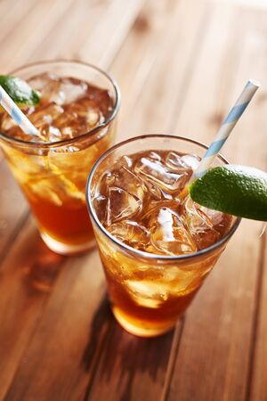 tea table: iced tea with lime wedge and retro paper straws close up Stock Photo