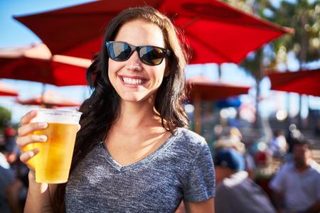 beer: retrato de mujer feliz celebración de taza de cerveza fuera en un día soleado