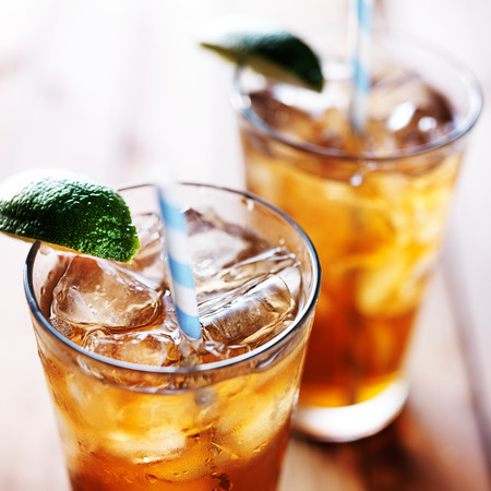 cold drink: iced tea with lime wedge and retro paper straws close up Stock Photo