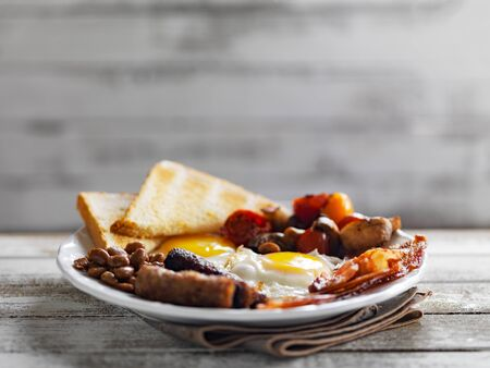 bacon baked beans: tasty english breakfast on rustic background with copy space composition Stock Photo