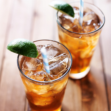 iced tea with lime wedge and retro paper straws close up Stock Photo