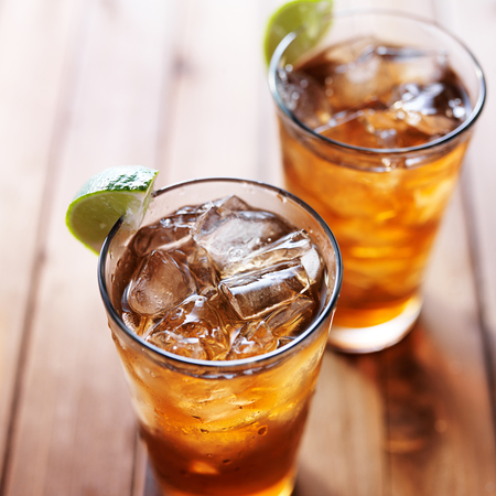 two glasses of iced tea with lime wedges on wooden table close up Stock Photo
