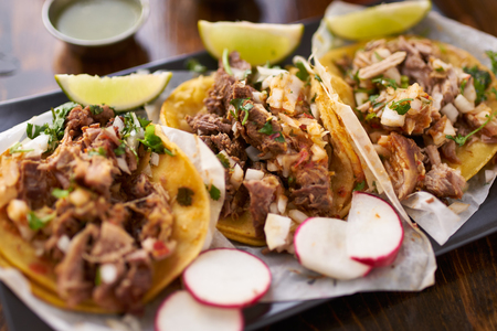 mexican street tacos with chicken, carnitas and barbacoa beef close up with radish slices