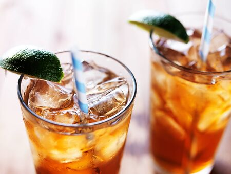 iced tea: iced tea with lime wedge and retro paper straws close up Stock Photo