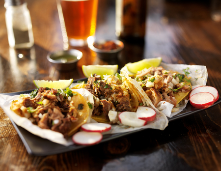 three tacos with beer on wooden table top served with limes and radishes