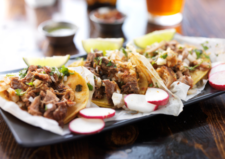 plate of authentic mexican street style tacos with radish slices