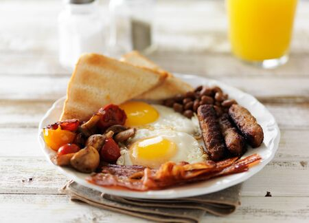 english breakfast: traditional english breakfast on rustic table with orange juice Stock Photo