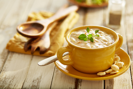 new england clam chowder with oyster crackers in yellow bowl Foto de archivo