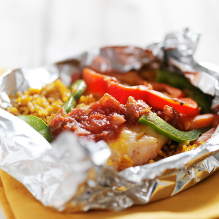 foil: baked mexican chicken fajitas with spanish rice in foil packet Stock Photo