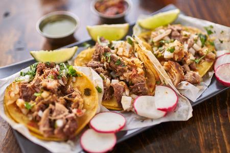 drei Straße Tacos in gelben Mais-Tortilla mit verschiedenen Fleischsorten
