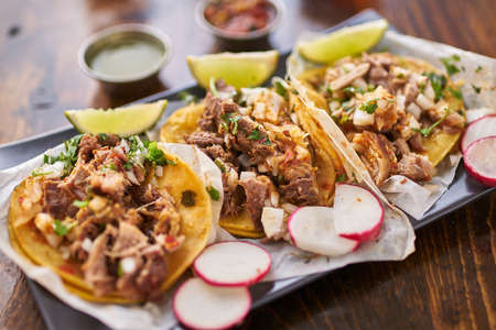 tortilla de maiz: tres tacos de la calle en tortilla de maíz amarillo con diferentes carnes Foto de archivo