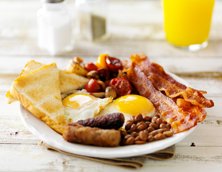 classic english breakfast on rustic table top served with orange juice Foto de archivo