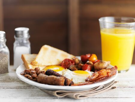 english breakfast: tasty english breakfast with eggs, bacon, baked beans, and sausages Stock Photo