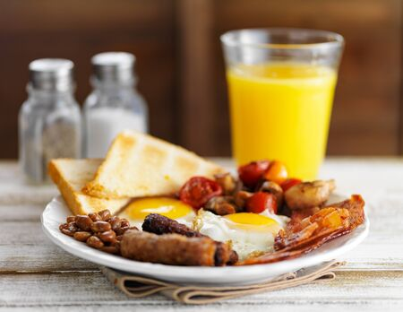 english breakfast: classic english breakfast on rustic table top served with orange juice Stock Photo