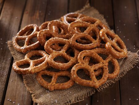 salty: pile of salted pretzels in rustic setting Stock Photo