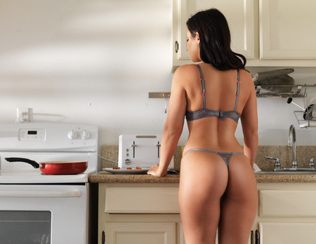 fille sexy nue: fille sexy lingerie porter cuisson du bacon dans la cuisine Banque d'images