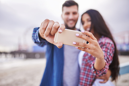couple selfie with selective focus on smart phone