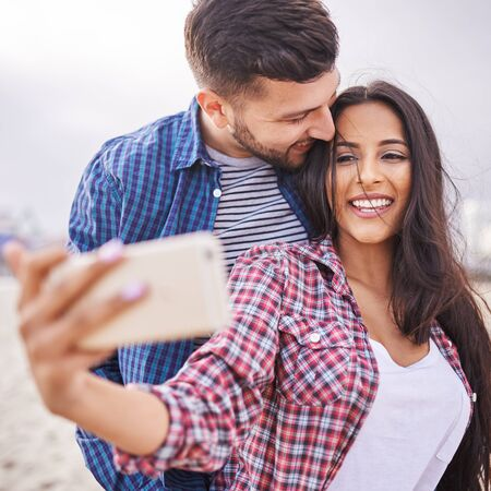 latina america: playful romantic couple taking selfies together Stock Photo